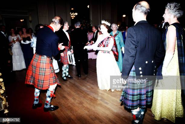 Queen Elizabeth II in a white dress and tartan sash takes to the floor with the Duke of Edinburgh in kilt during the Centenary Ball of the Scottish...
