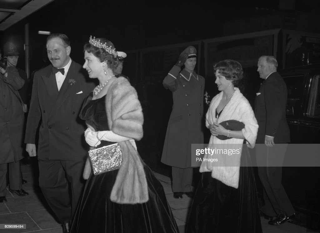 Queen Elizabeth II, in black velvet and with a diamond tiara and grey fur stole, arrives with Princess Margaret for the special charity performance of the film 'Gigi', at the Columbia Theatre, Shaftesbury Avenue, London. Princess Margaret also wears black velvet, but with an ermine stole. The performance is in aid of the Family Welfare Association.