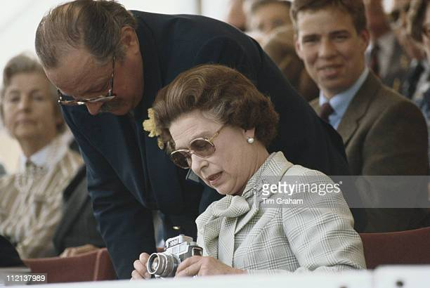 Queen Elizabeth II inspecting her Leica camera at the Royal Windsor Horse Show held at Home Park in Windsor Berkshire England Great Britain 6 May 1982