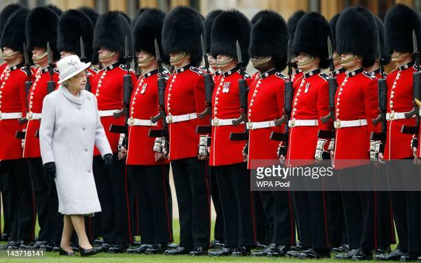Queen Elizabeth II inspects the guards during a ceremony to present new colours to the 1st Battalion and No 7 Company the Coldstream Guards at...