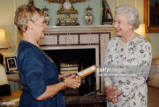 Queen Elizabeth II invests Dame Judi Dench with the Insignia of a Companion of Honour at Buckingham Palace