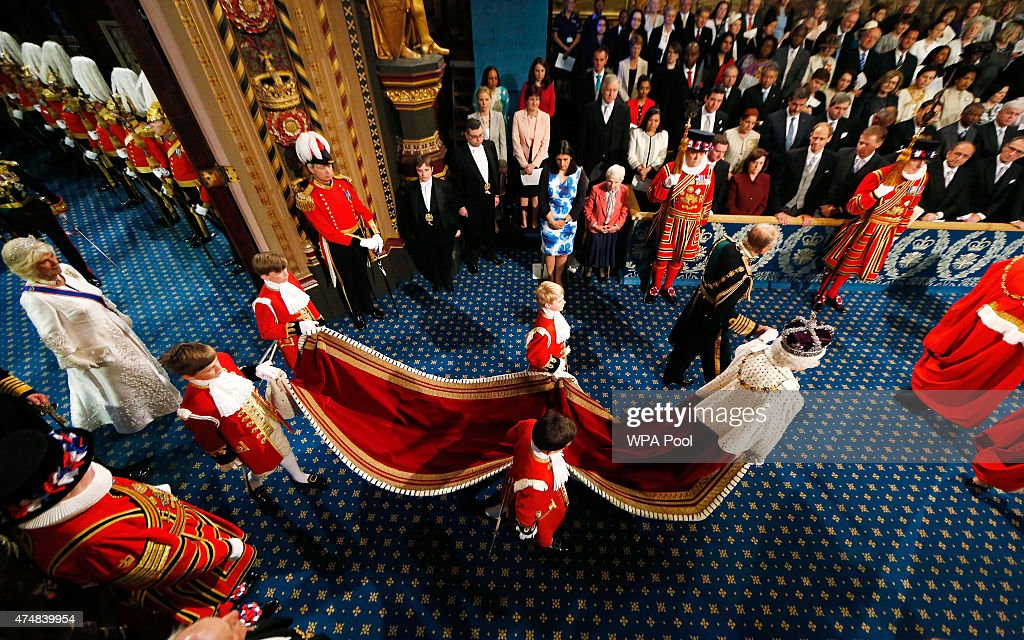 Queen Elizabeth II is accompanied by Prince Philip, Duke of Edinburgh as they proceed through the Royal Gallery before the State Opening of Parliament in the House of Lords, at the Palace of Westminster on May 27, 2015 in London, England.
