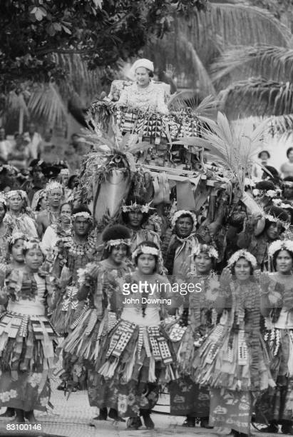 Queen Elizabeth II is carried through the streets on a litter during a trip to Fiji 1st November 1982
