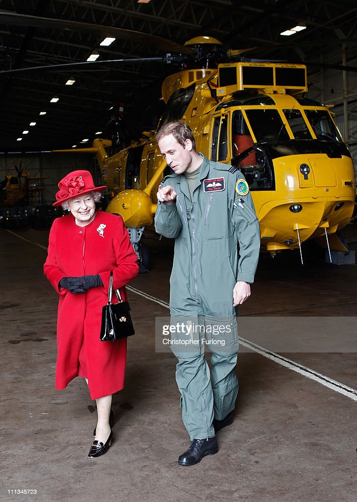 Queen Elizabeth II is escorted by her grandson Prince William during a visit to RAF Valley where Prince William is stationed as a search and rescue helicopter pilot on April 1, 2011 in Holyhead, United Kingdom. The Queen toured the airbase meeting staff and families, watched a fly past and was given a guided tour of a Sea King search and rescue helicopter by Prince William.