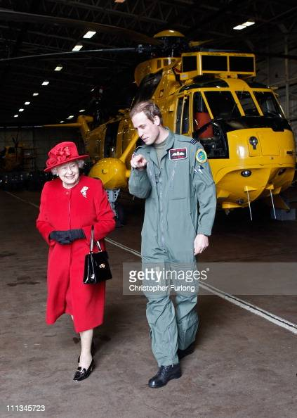 Queen Elizabeth II is escorted by her grandson Prince William during a visit to RAF Valley where Prince William is stationed as a search and rescue...