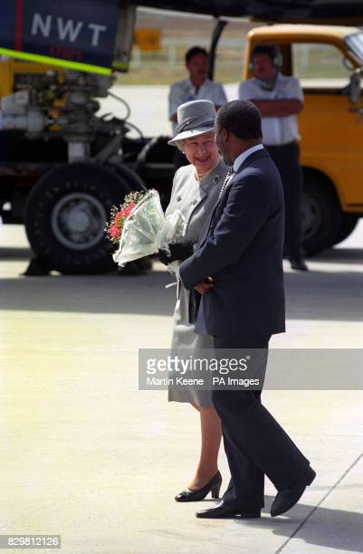 Queen Elizabeth II is escorted by South Africa's Deputy President Thabo Mbeki as she walks on South African soil for the first time since 1947 on her...