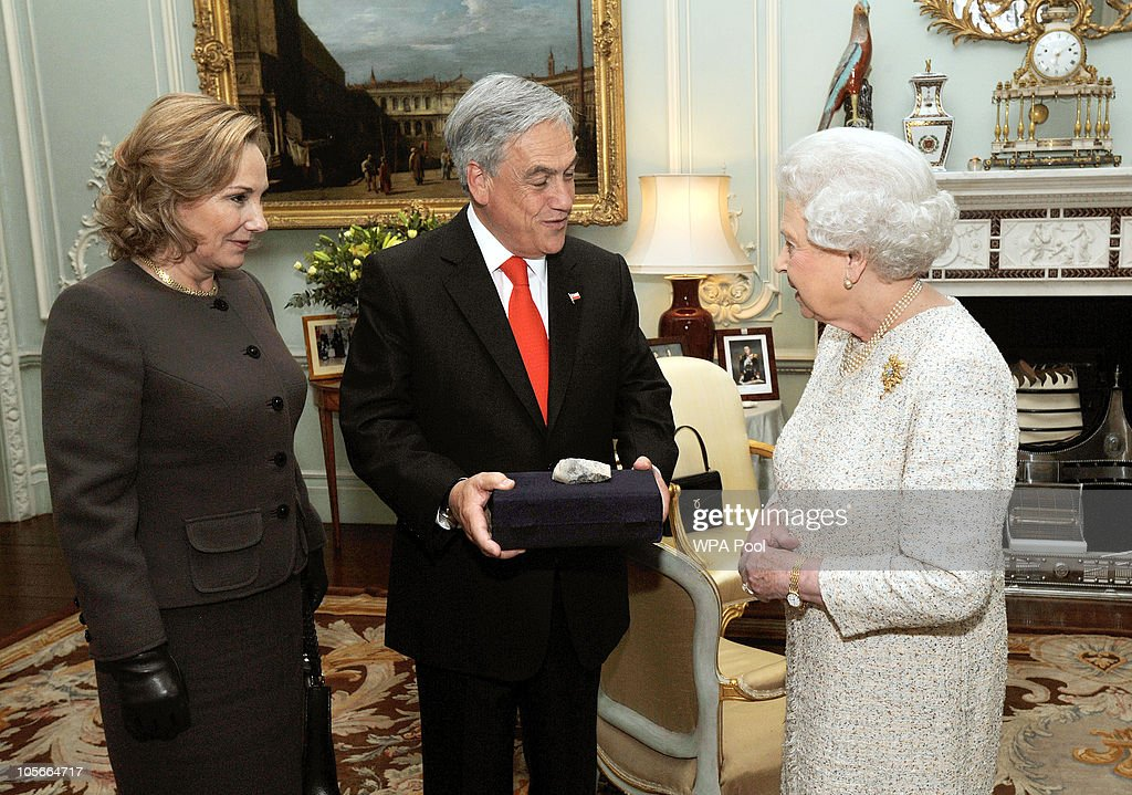 Queen Elizabeth II is given a piece of rock from the San Jose Mine by the President of Chile, Sebastian Pinera, accompanied by his wife Cecilia Morel Montes during a private meeting at Buckingham Palace on October 18, 2010 in London. The rock comes from the bottom of the collapsed mine where 33 men were trapped for more than two months. Earlier PRime Minister David Cameron gave Pinera 33 bottles of British beer.
