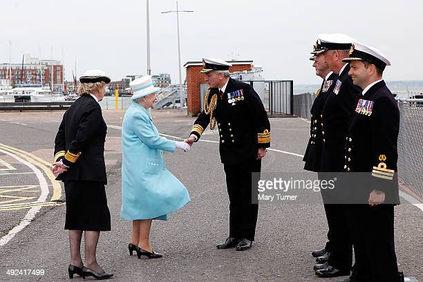 Queen Elizabeth II is greeted by Commodore Jeremy Rigby as she arrives at Portsmouth Naval Base for a visit to HMS Lancaster on May 20 2014 in...