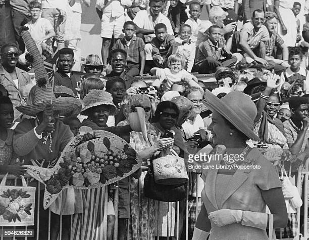 Queen Elizabeth II is greeted by crowds at the Straw Market on Bay Street as she arrives in Nassau for a twoday visit to the Bahamas during a tour of...
