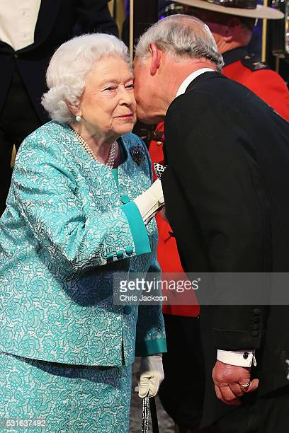 Queen Elizabeth II is greeted by Prince Charles Prince of Wales as she arrives to attend a 90th Birthday Celebration show at Windsor Castle on May 15...