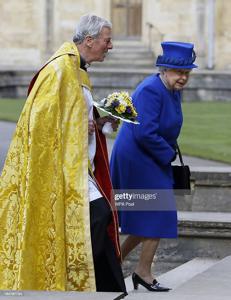 Queen Elizabeth II is greeted by The Dean Christopher Lewis as she arrives to attend the Maundy service, at Christ Church Cathedral on March 28, 2013 in Oxford, England. The Maundy money was today distributed by the Queen to 87 women and 87 men, who each received two purses, one red and one white. A 5 GBP coin and 50 pence coin commemorating the 60th anniversary of The Queen's Coronation in the red purse. The white purse contains the uniquely minted Maundy Money. This takes the form of silver one, two, three and four penny pieces, the sum of which equals the number of years the Monarch's age.