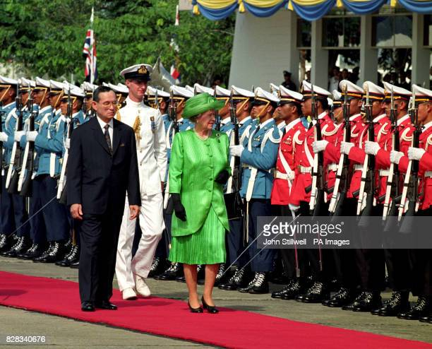 Queen Elizabeth II is greeted by the Thai King Bhumibol in Bangkok after her arrival in Thailand
