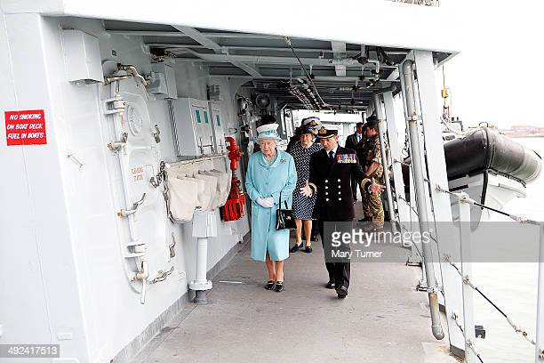 Queen Elizabeth II is guided on board HMS Lancaster by its Commanding Officer Commander Peter Laughton at Portsmouth Naval Base where the queen...