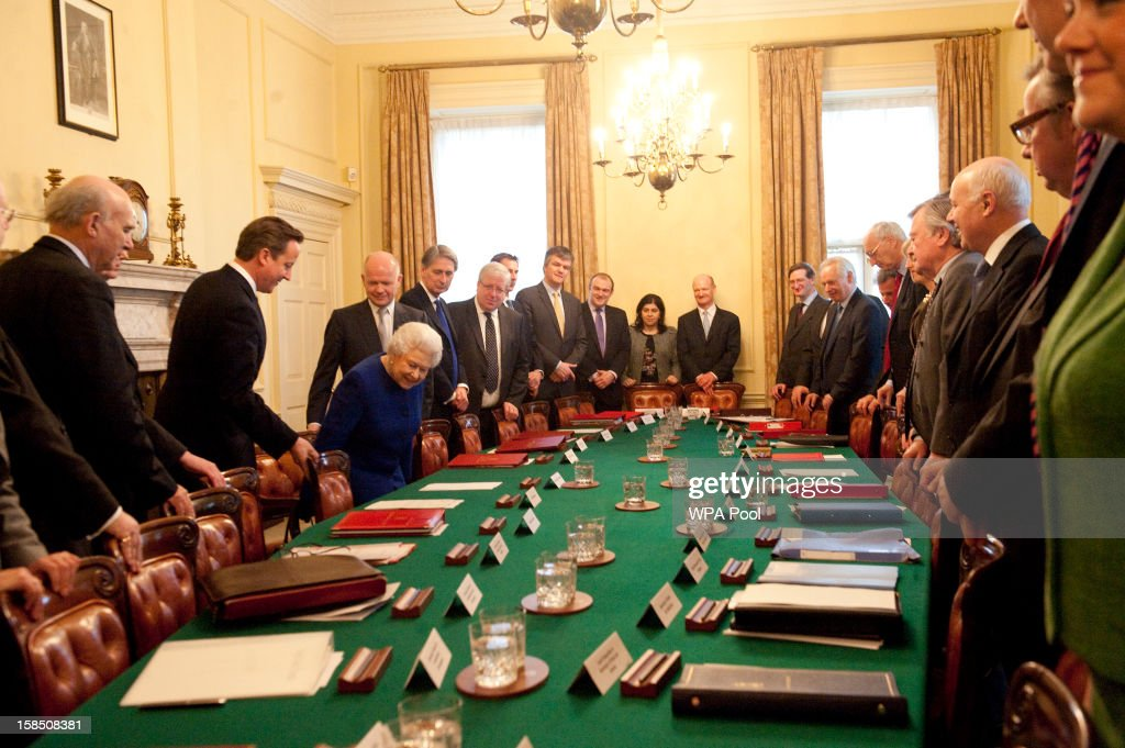 Queen <a gi-track='captionPersonalityLinkClicked' href=/galleries/search?phrase=Elizabeth+II&family=editorial&specificpeople=67226 ng-click='$event.stopPropagation()'>Elizabeth II</a> is helped to her seat by British Prime Minister <a gi-track='captionPersonalityLinkClicked' href=/galleries/search?phrase=David+Cameron+-+Politician&family=editorial&specificpeople=227076 ng-click='$event.stopPropagation()'>David Cameron</a> as she arrives at Number 10 Downing Street to attend the Government's weekly Cabinet meeting on December 18, 2012 in London, England. The Queen's visit to the weekly Cabinet meeting as an observer is the first time a monarch has attended the meeting since Queen Victoria's reign.