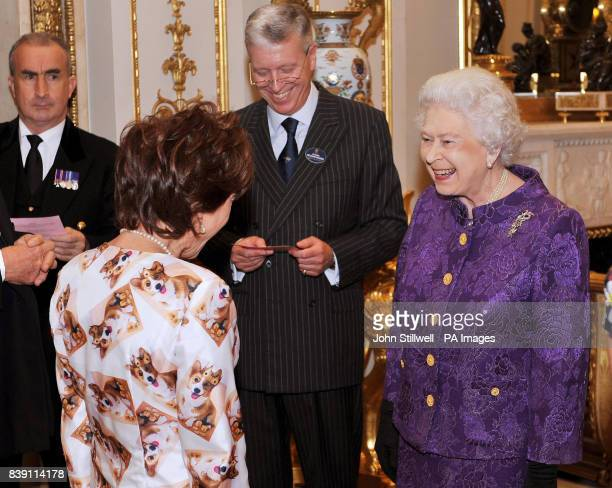 Queen Elizabeth II is impressed by the Corgi in a Crown outfit worn by Kathy Lette in the white drawing room at Buckingham Palace before a Royal...