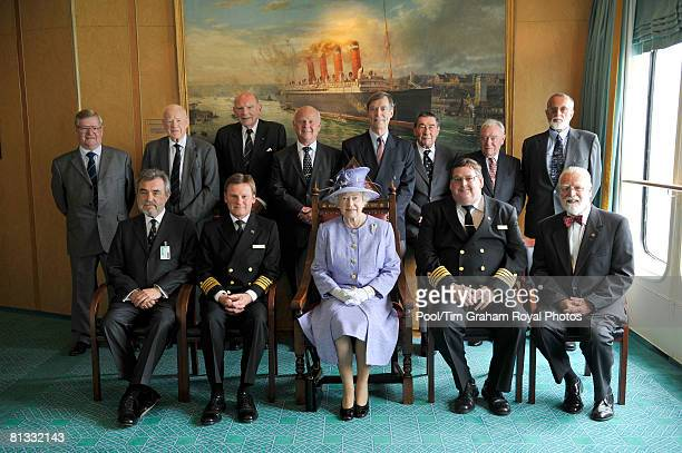 Queen Elizabeth II is photographed with former captains of the QE2 during a visits to ocean liner in Southampton dock on June 2 2008 in Southampton...