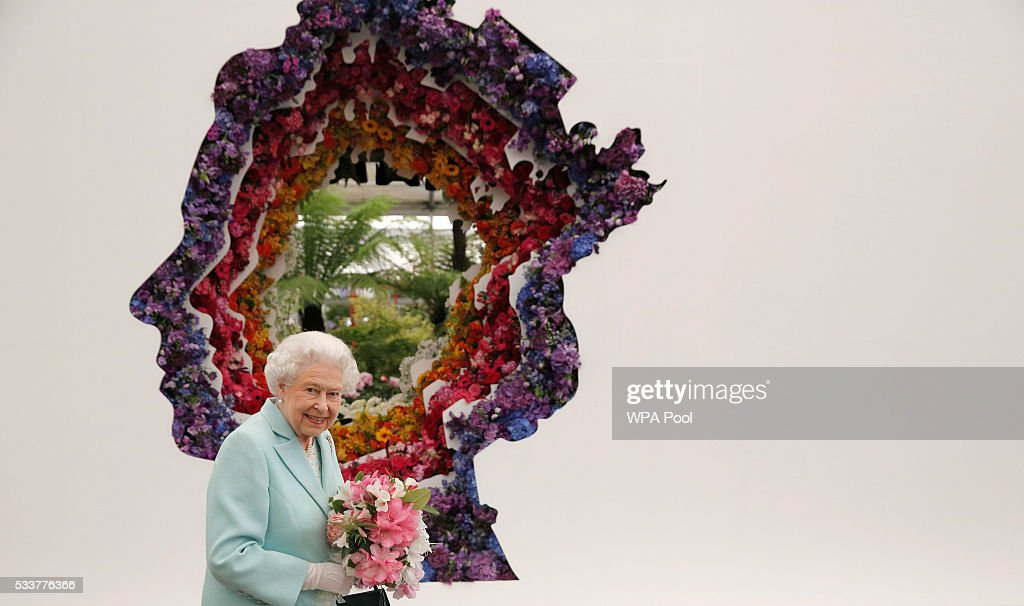 Queen Elizabeth II is pictured next to a floral exhibit by the New Covent Garden Flower Market, which features an image of the Queen, at Chelsea Flower Show press day at Royal Hospital Chelsea on May 23, 2016 in London, England. The show, which has run annually since 1913 in the grounds of the Royal Hospital Chelsea, is open to the public from 24-28 May.