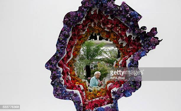 Queen Elizabeth II is pictured through a gap in a floral exhibit by the New Covent Garden Flower Market which features an image of the Queen at...