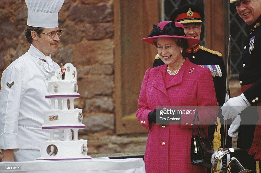 Queen Elizabeth II is presented with a birthday cake by the men of the Royal Welch Fusiliers, during a visit to Powis Castle in Wales, 21st April 1989.