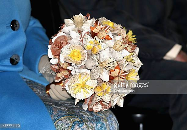 Queen Elizabeth II is presented with a 'technology themed' bouquet of as she visits the 'Information Age' Exhibition at the Science Museum on October...