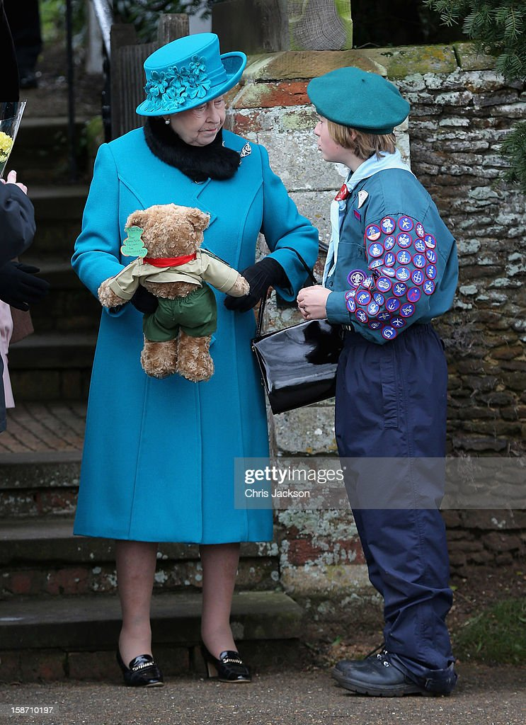 Queen Elizabeth II is presented with a teddy bear by a scout as she leaves St Mary Magdalene Church after attending the traditional Christmas Day church service on December 25, 2012 in Sandringham near King's Lynn, England.