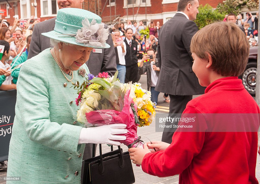 Queen Elizabeth II is presented with flowers as she leaves the Cardiff University Brain Research Imaging Centre CUBRIC after officially open the new £44 million centre on June 7, 2016 in Cardiff, Wales.