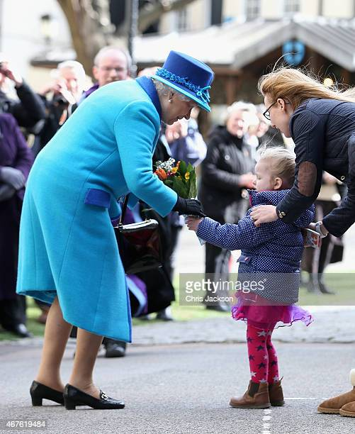 Queen Elizabeth II is presented with flowers by a young girl as she visits Canterbury Cathedral on March 26 2015 in Canterbury England