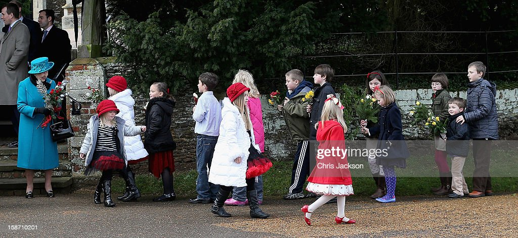 Queen <a gi-track='captionPersonalityLinkClicked' href=/galleries/search?phrase=Elizabeth+II&family=editorial&specificpeople=67226 ng-click='$event.stopPropagation()'>Elizabeth II</a> (L) is presented with flowers by children as she leaves St Mary Magdalene Church after attending the traditional Christmas Day church service on December 25, 2012 in Sandringham near King's Lynn, England.