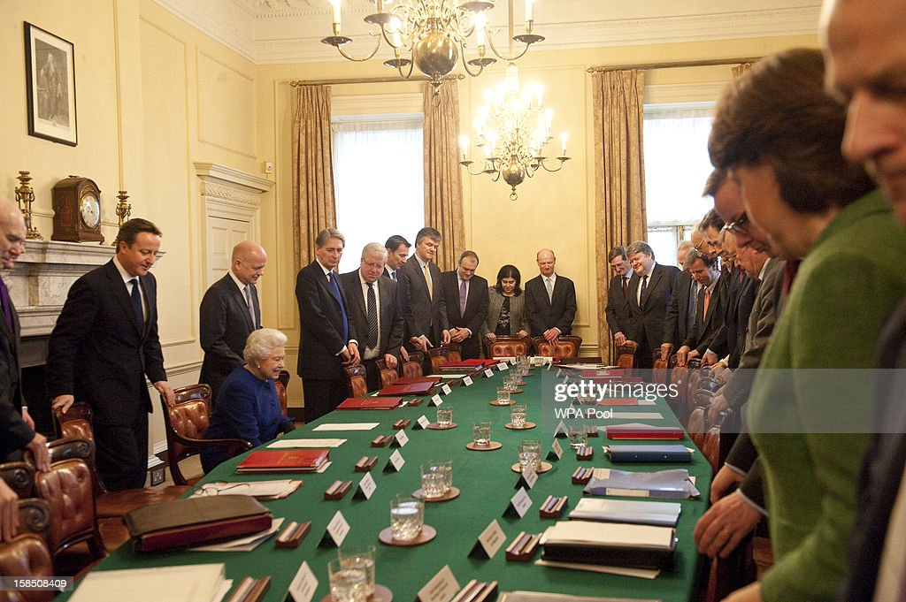 Queen Elizabeth II is seated as British Prime Minister David Cameron and other members of the cabinet look on at Number 10 Downing Street to attend the Government's weekly Cabinet meeting on December 18, 2012 in London, England. The Queen's visit to the weekly Cabinet meeting as an observer is the first time a monarch has attended the meeting since Queen Victoria's reign.