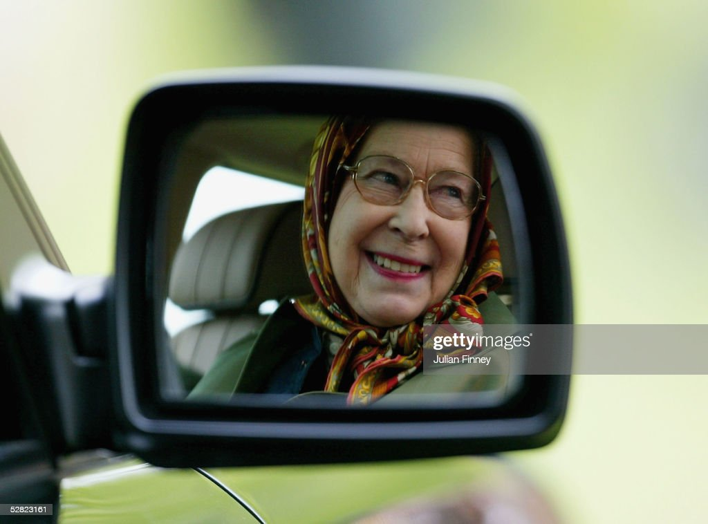 Queen Elizabeth II Is Seen Reflected In The Wing Mirror Of Her Land Rover As She