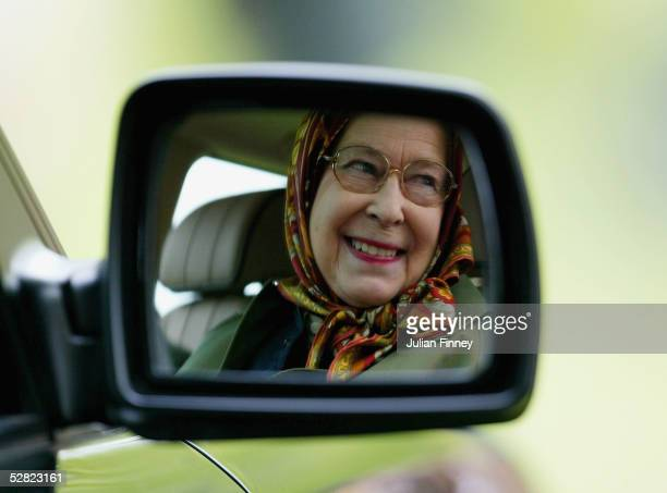 Queen Elizabeth II is seen reflected in the wing mirror of her Land Rover as she follows The Duke of Edinburgh as he competes in the Driving Grand...
