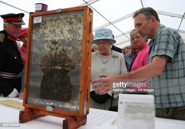 Queen Elizabeth II is shown bees by Aberdeen Bee Keepers Association's David Findlater as she visited the 150th Anniversary Turriff Show in Turriff...