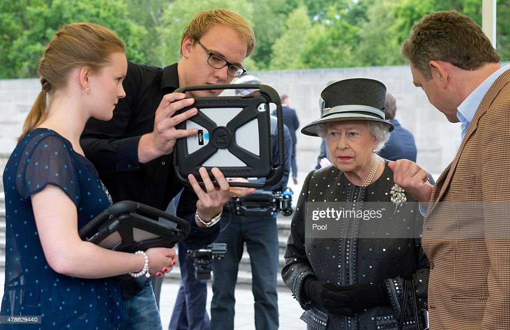 Queen Elizabeth II is shown by India Stutzke, 17, and Nils Scholl, 18, from the Kaiserin-Auguste-Viktoria-Gymnasium in Celle and developer Paul Verschure (R) on a tablet computer how the concentration camp has looked like in earlier days during a visit of the concentration camp memorial at Bergen-Belsen on June 26, 2015 in Lohheide, Germany. The Queen and The Duke of Edinburgh viewed the grave of Anne Frank and laid a wreath at the inscription wall, before they met two survivors of the camp and as well as two liberators. This is the final day of a four day state visit, which is their first to Germany since 2004.