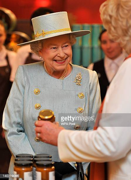 Queen Elizabeth II is shown jars of preserves while visiting Fortnum Mason store on March 1 2012 in London England Together with Camilla Duchess of...