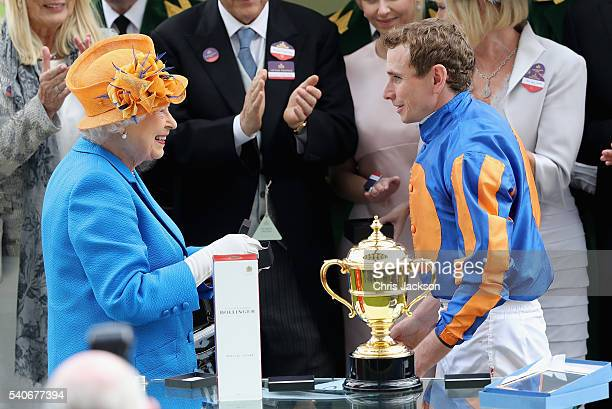 Queen Elizabeth II jokes with Gold Cup winning jockey Ryan Moore in the parade ring as she attends the third day of Royal Ascot at Ascot Racecourse...