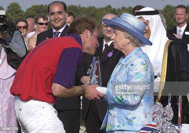 Queen Elizabeth II kisses her grandson Prince William as they attend a polo match at Windsor Great Park following the second day of Royal Ascot at...