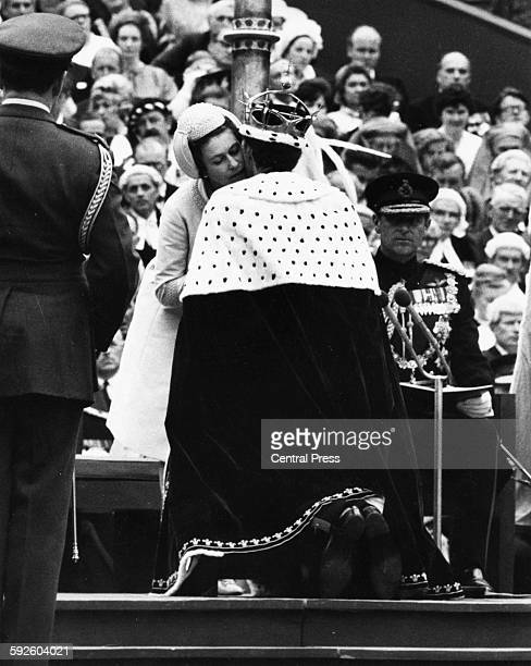 Queen Elizabeth II kissing Prince Charles on the cheek as she pins the blue and ermine cape around his neck as he is invested as the Prince of Wales...