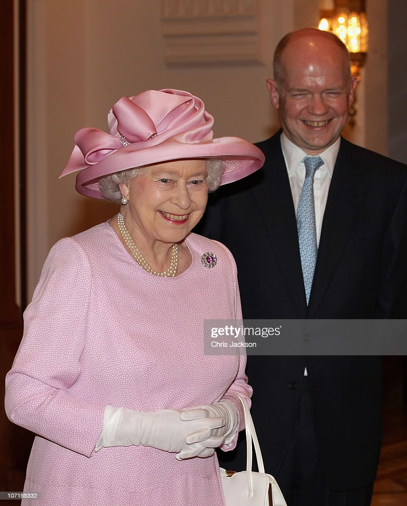 Queen Elizabeth II laughs with Foreign & Commonwealth Secretary <a gi-track='captionPersonalityLinkClicked' href=/galleries/search?phrase=William+Hague&family=editorial&specificpeople=206295 ng-click='$event.stopPropagation()'>William Hague</a> during a Tate Gallery event as they visit Al-Alam Palace on November 26, 2010 in Muscat, Oman. Queen Elizabeth II and Prince Philip, Duke of Edinburgh are on a State Visit to the Middle East. The Royal couple have spent two days in Abu Dhabi and three days in Oman.