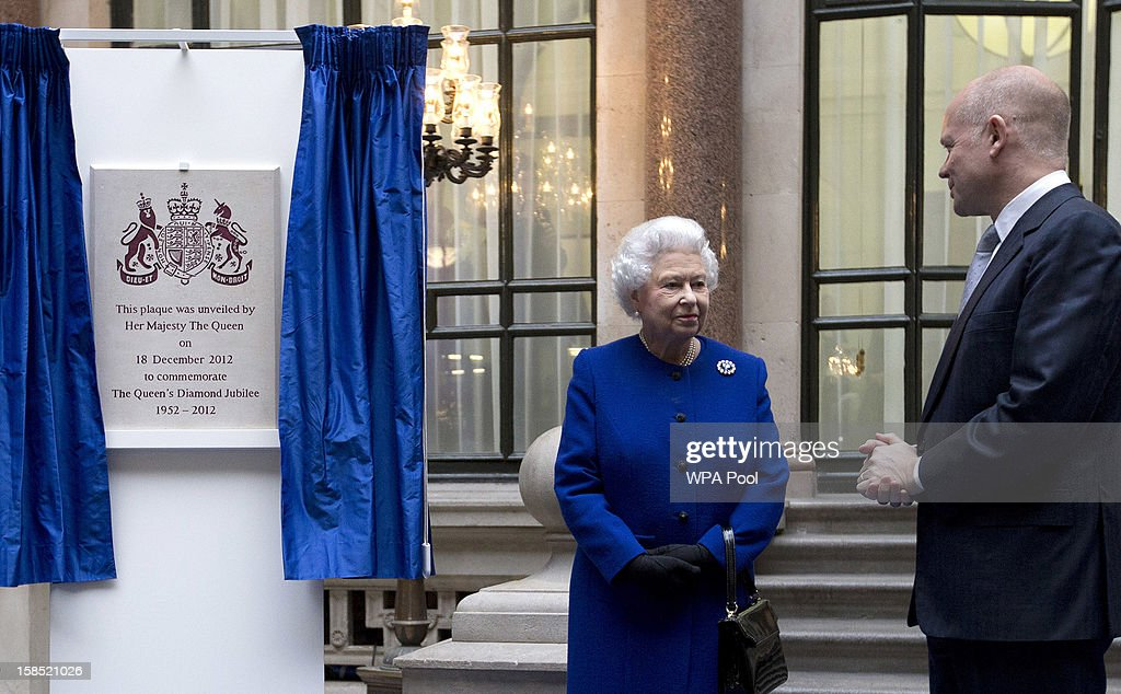 Queen Elizabeth II listens to British Foreign Secretary William Hague after unveiling a plaque to commemorate her visit of The Foreign and Commonwealth Office during an official visit which is part of her Jubilee celebrations on December 18, 2012 in London, England.
