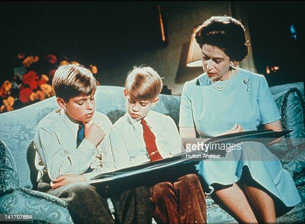 Queen Elizabeth II looking at a photograph album with her sons Prince Andrew and Prince Edward December 1971 Footage of this scene was used in the...