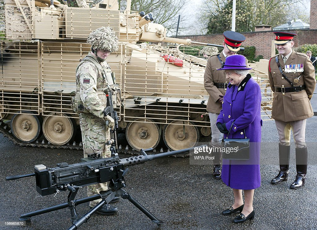 Queen Elizabeth II looks at a machine gun as she meets members of the Household Cavalry at Combermere Barracks on November 26, 2012 in Windsor, England.