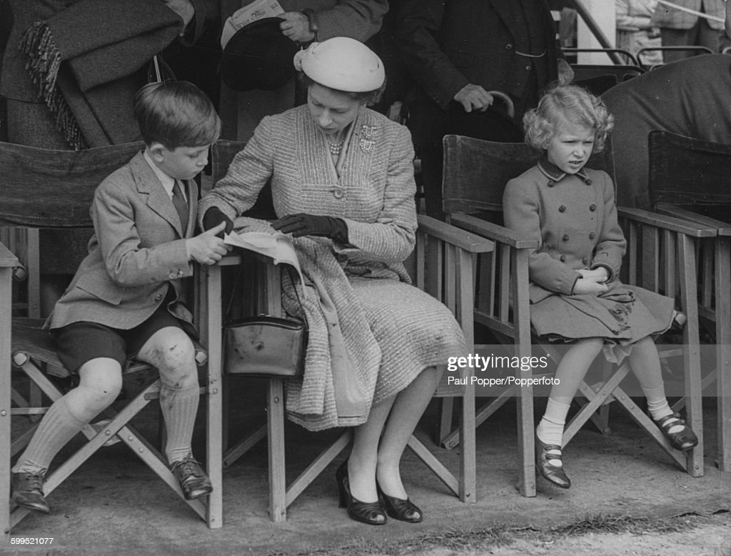 Queen Elizabeth II Looks At A Program With Prince Charles As They And Princess Anne Watch