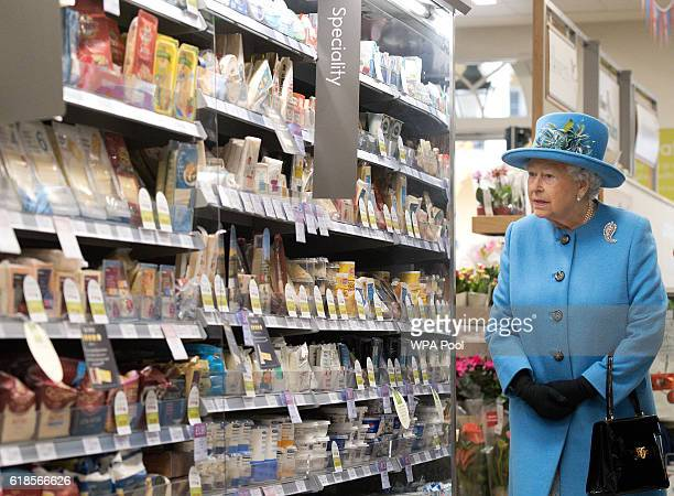 Queen Elizabeth II looks at products on the shelves at a Waitrose supermarket during a visit to the town of Poundbury on October 27 2016 in Poundbury...