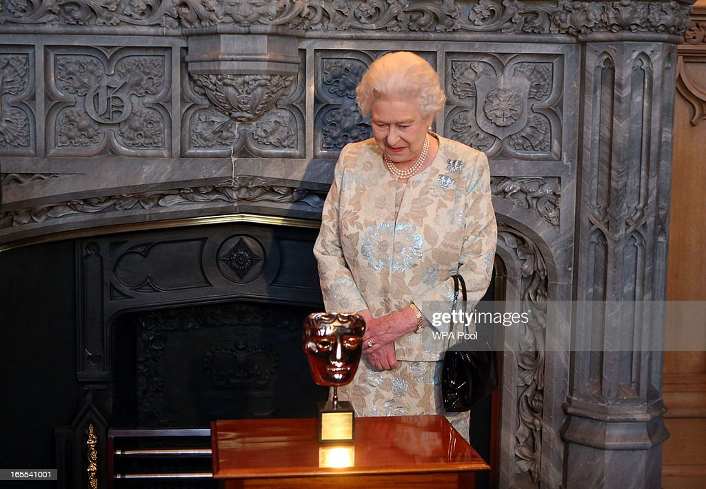 Queen <a gi-track='captionPersonalityLinkClicked' href=/galleries/search?phrase=Elizabeth+II&family=editorial&specificpeople=67226 ng-click='$event.stopPropagation()'>Elizabeth II</a> looks at the BAFTA that she received in recognition for a lifetime's support of British Film and Television at a reception for the British Film Industry at Windsor Castle on April 4, 2013 in Berkshire, England.