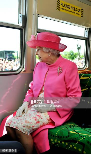 Queen Elizabeth II looks at the huge crowd of well wishers as she and the Duke of Edinburgh ride on an electric Tram through the Melbourne city...