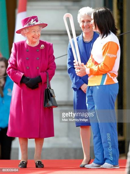 Queen Elizabeth II looks on as former track cyclist Anna Meares of Australia holds The Queen's Baton during the launch of The Queen's Baton Relay for...