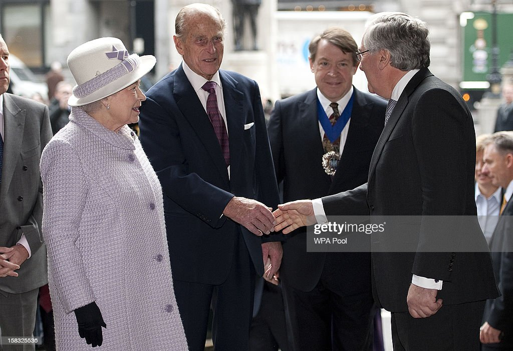 Queen Elizabeth II looks on as Governor, Sir Mervyn King shakes hands with Prince Philip, Duke of Edinburgh as they visit the Bank of England on December 13, 2012 in London, England. Governor, Sir Mervyn King met with the Queen and Duke before they visited the Banking Hall to discuss payment system controls. The royal couple viewed banknotes, counterfeit currency, a gold vault, historical items, met with gold experts, security staff and the Market Operations Office while on their visit to the Bank of England.