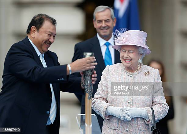 Queen Elizabeth II looks on as Prince Imran President of the Commonwealth Games Federation closes the baton after she placed her message inside for...