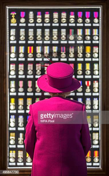 Queen Elizabeth II looks upon a cabinet of medals during a visit to the medal room in the Ministry of defence medal office at the joint casualty and...
