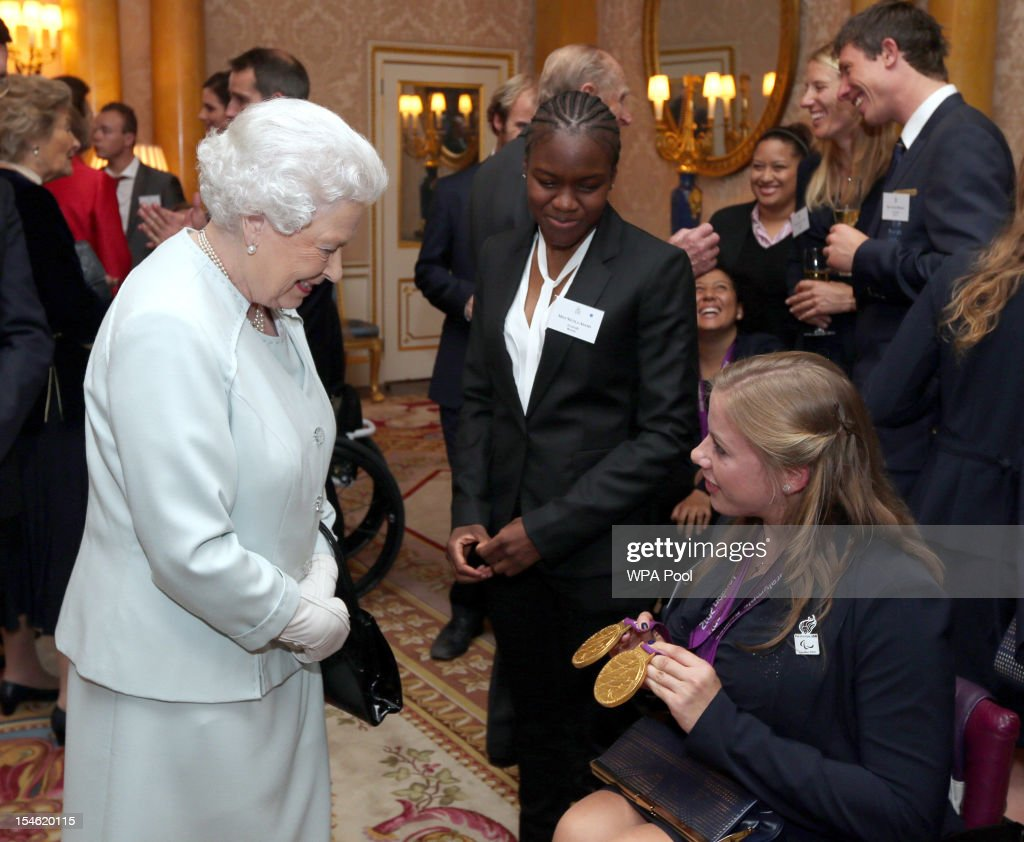 Queen Elizabeth II meets boxer Nicola Adams and paralympian Hannah Cockcroft during a reception for the Team GB Olympic and Paralympic medalists at Buckingham Palace on October 23, 2012 in London, England.